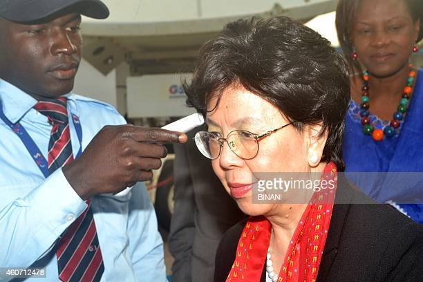 Margaret Chan director general of the World Health Organization has her temperature checked as she arrives in Conakry on December 20 during a tour of...