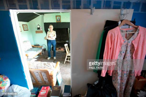 Margaret Gallagher poses for a photograph in front of the open fireplace in her three roomed thatched cottage near the village of Belcoo Enniskillen...