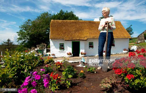 Margaret Gallagher poses for a photograph in her garden in front of her three roomed thatched cottage near the village of Belcoo Enniskillen northern...