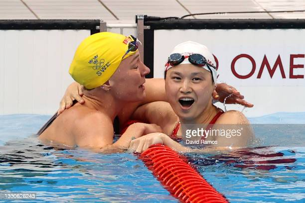 Margaret Macneil of Team Canada and Sarah Sjoestroem of Team Sweden react after the Women's 100m Butterfly Final on day three of the Tokyo 2020...