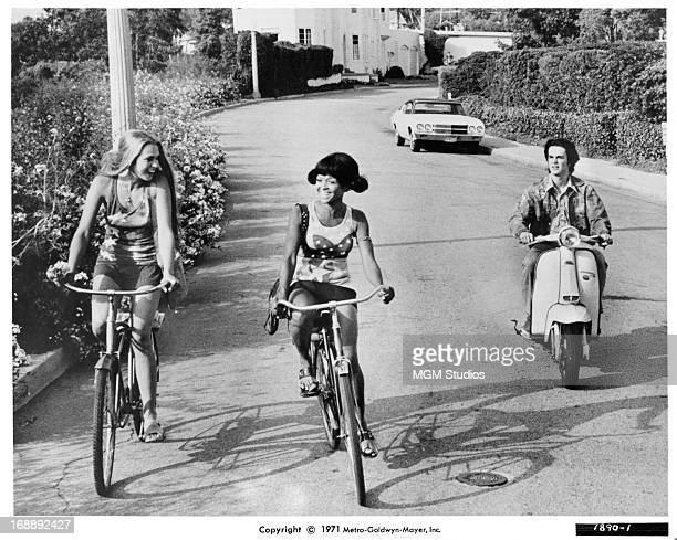 Margaret Markov bikes with her friend as John David Carson follows behind in a scene from the film 'Pretty Maids All In A Row' 1971