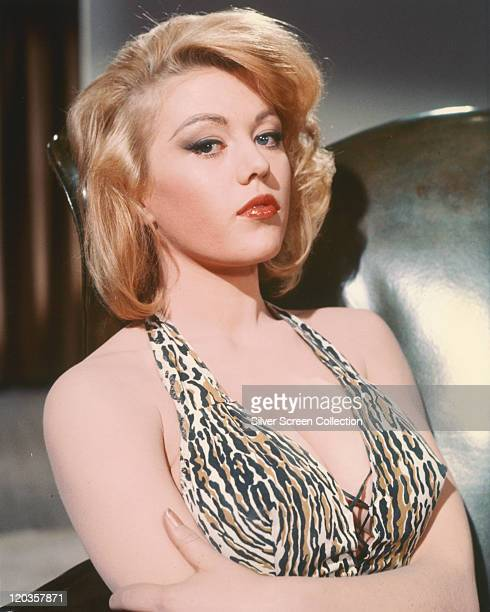 Margaret Nolan, British actress and glamour model, wearing a tiger print halterneck top, with her arms crossed, circa 1965.