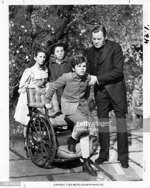 Margaret O'Brien and Brian Roper watch as Dean Stockwell attempts to walk with the help of Herbert Marshall in a scene from the film 'The Secret...