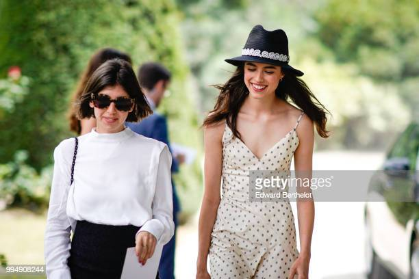 Margaret Qualley wears a hat a white dress with black polka dots outside Dior during Paris Fashion Week Haute Couture Fall Winter 2018/2019 on July 2...