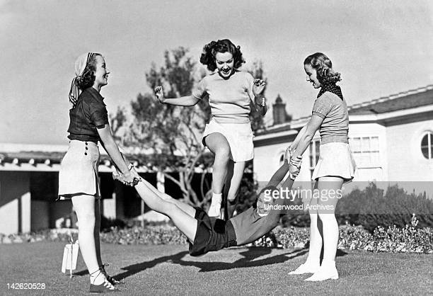 Margaret Randall and Marion Weldon swing Paula De Cardo as a human jump rope for Gwen Kenyon to celebrate the completion of the Paramount picture...