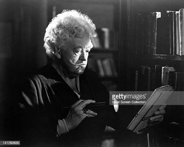 Margaret Rutherford , British actress, reading the cover of a book by torch light, in a publicity still issued for the film, 'Murder Ahoy!', Great...