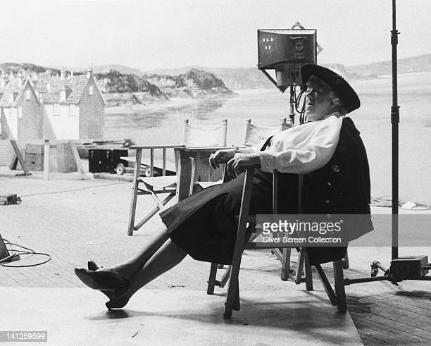 Margaret Rutherford British actress relaxing in a chair on the set of a film her legs outstretched before her with a coastal view in the background...