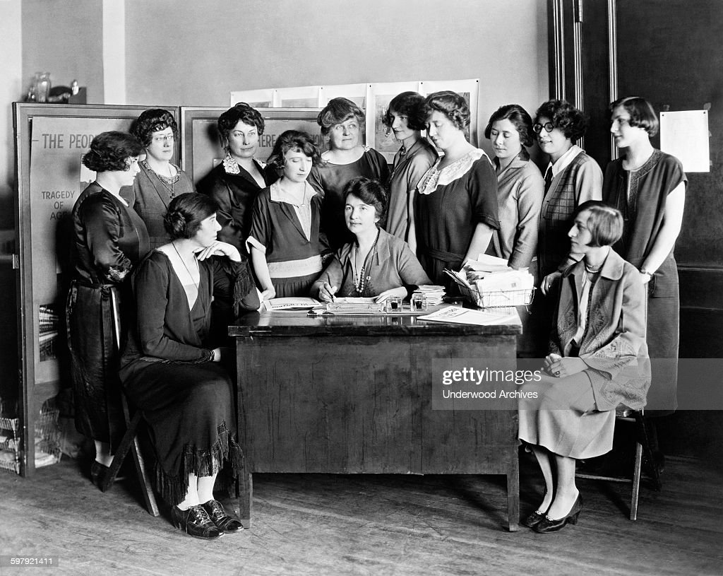 Margaret Sanger seated behind a desk and surrounded by twelve other women, New York, New York, circa 1924.