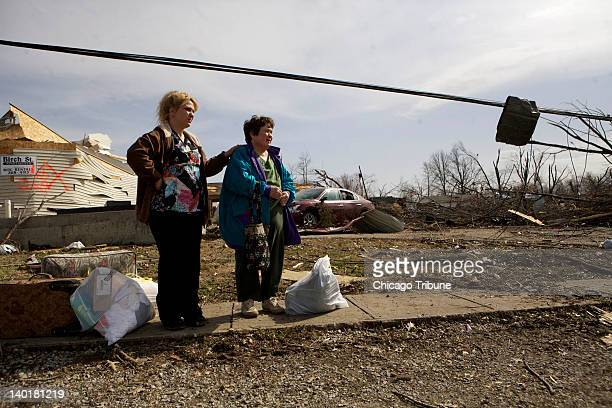 Margaret Shimkus left and her daughter Julie Shaw stand in front of Shimkus's house after a tornado ripped through Harrisburg Illinois early...