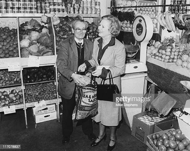Margaret Thatcher Leader of the Conservative Party visits her local greengrocer's in Kensington London 7th April 1979 Shopkeeper G Poole helps her...