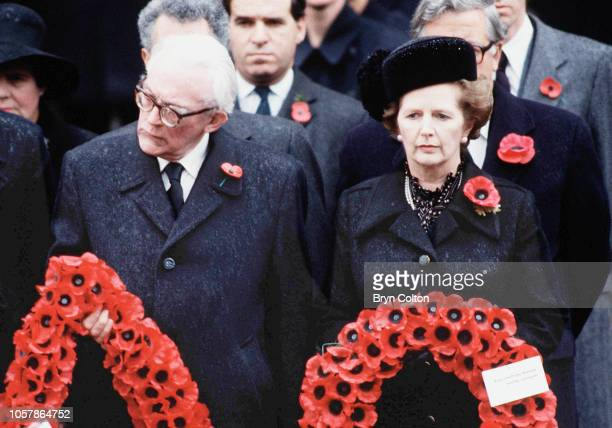 Margaret Thatcher UK Prime Minister right stands with Labour leader Michael Foot both holding poppy wreath's during the Remembrance Day service at...