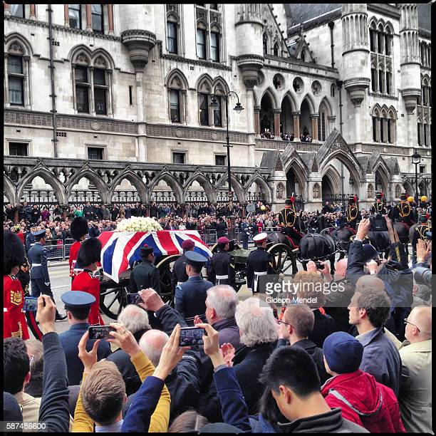 Margaret Thatcher's coffin draped with a Union Jack flag is ceremonially pulled by a gun carriage past the Royal Courts of Justice on Fleet Street en...