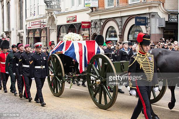 Margaret Thatcher's coffin is wheeled along on a gun carriage by horses, flanked by military personnel on both sides.