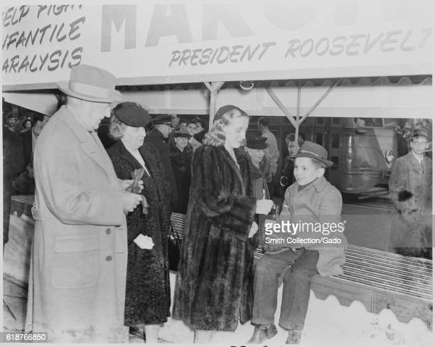 Margaret Truman daughter of President Harry Truman and First Lady Bess Truman drops a coin into a bottle held by a young boy during a public...