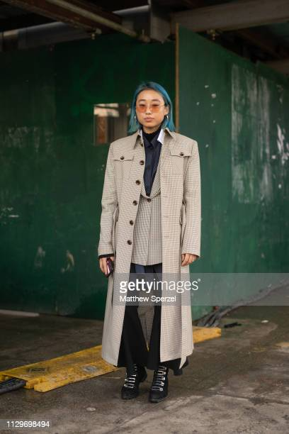 Margaret Zhang is seen on the street during New York Fashion Week AW19 wearing taupe trench coat with blazer and navy vest on February 13, 2019 in...