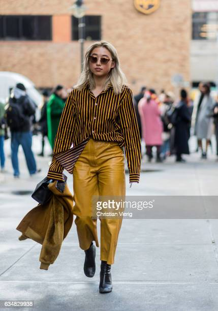 Margaret Zhang wearing a mustard striped button shirt mustard pants outside Dion Lee on February 11 2017 in New York City