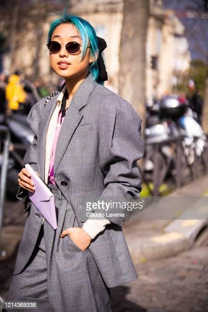 Margaret Zhang, wearing a pied de poule suit, is seen outside Miu Miu, during Paris Fashion Week - Womenswear Fall/Winter 2020/2021 : Day Nine on...
