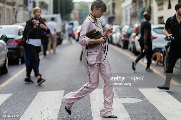 Margaret Zhang wearing a pink pyjama and Prada bag outside Prada during the Milan Men's Fashion Week Spring/Summer 2017 on June 19 2016 in Milan Italy