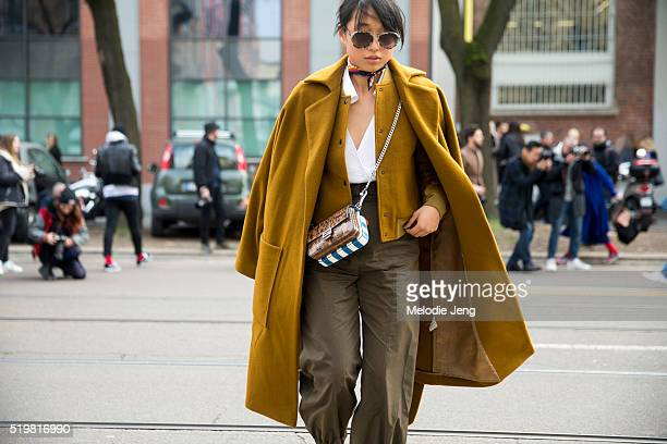 Margaret Zhang wears a mustard yellow coat and jacket with a white top and Fendi army green trousers at the Fendi show during the Milan Fashion Week...