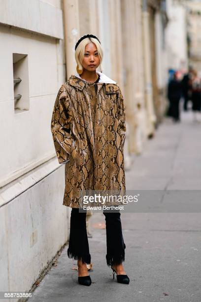 Margaret Zhang wears a snake print coat flare pants outside Valentino during Paris Fashion Week Womenswear Spring/Summer 2018 on October 1 2017 in...