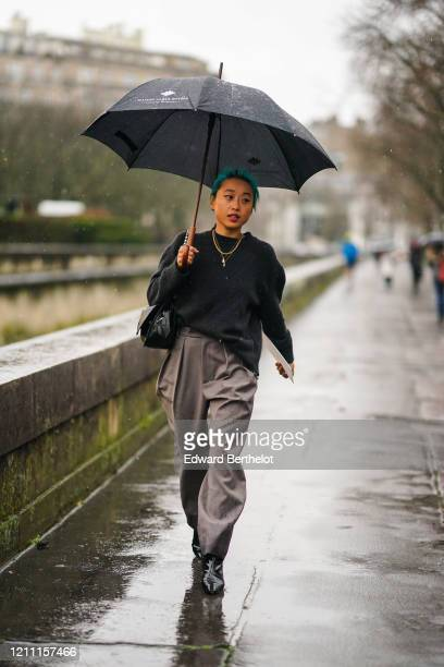 Margaret Zhang wears an oversized pullover, a necklace, gray flowing pants, black leather pointy boots, a bag, outside Valentino, during Paris...