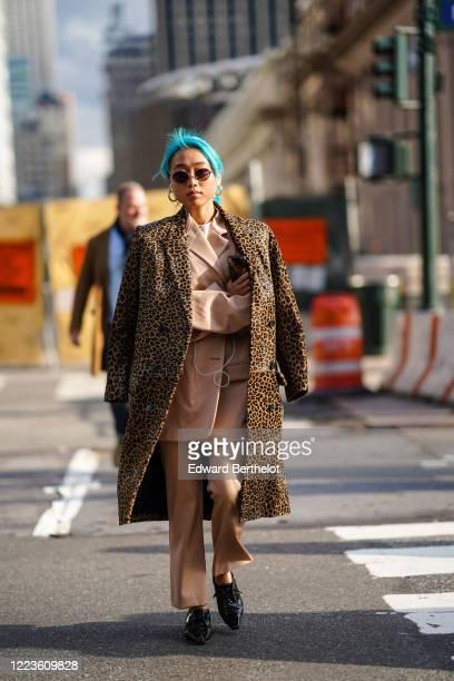 Margaret Zhang wears sunglasses, a brown leopard print oversized long coat, a pale pastel pink oversized jacket, suit pants, black pointy shoes,...