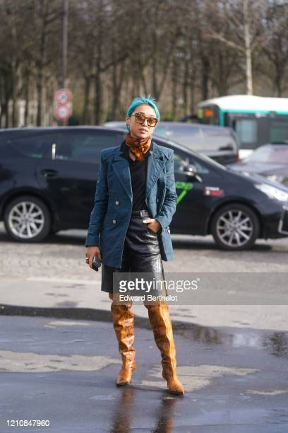 Margaret Zhang wears sunglasses, a brown scarf, a blue jacket with buttons, a black leather skirt, brown leather pointy boots, outside Chanel, during...