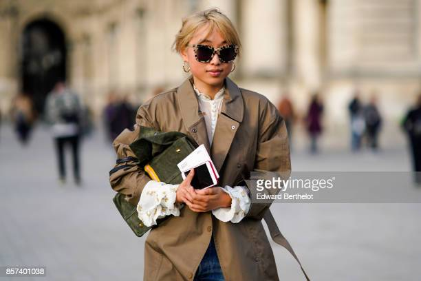 Margaret Zhang wears sunglasses a trench coat blue jeans outside Louis Vuitton during Paris Fashion Week Womenswear Spring/Summer 2018 on October 3...