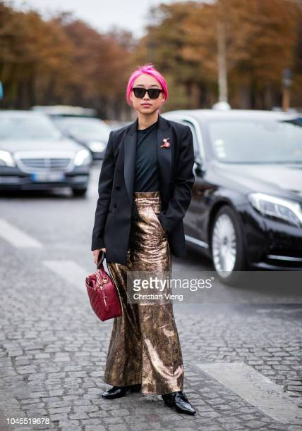Margaret Zhang with pink hair wearing black blazer, red Chanel bag, golden wide leg pants is seen outside Chanel during Paris Fashion Week Womenswear...