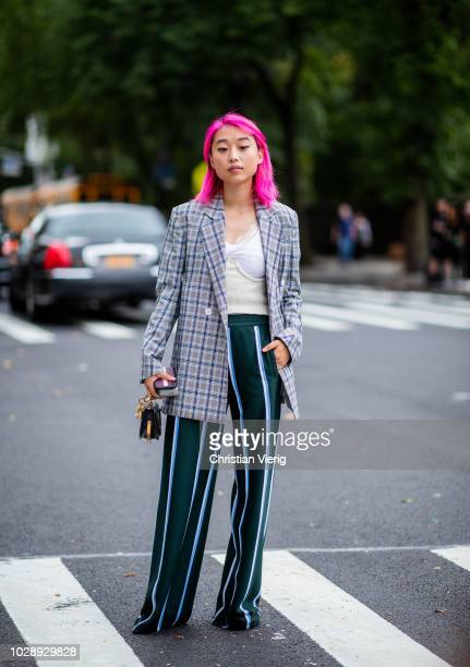 Margaret Zhang with pink hair wearing checked blazer, striped pants is seen outside Tory Burch during New York Fashion Week Spring/Summer 2019 on...