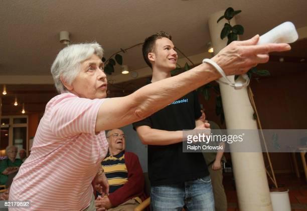 Margarete Roeder , standing next to student Markus Deindl plays Nintendo Wii bowling at the Malhaelden seniors home on August 4, 2008 in Pforzheim,...