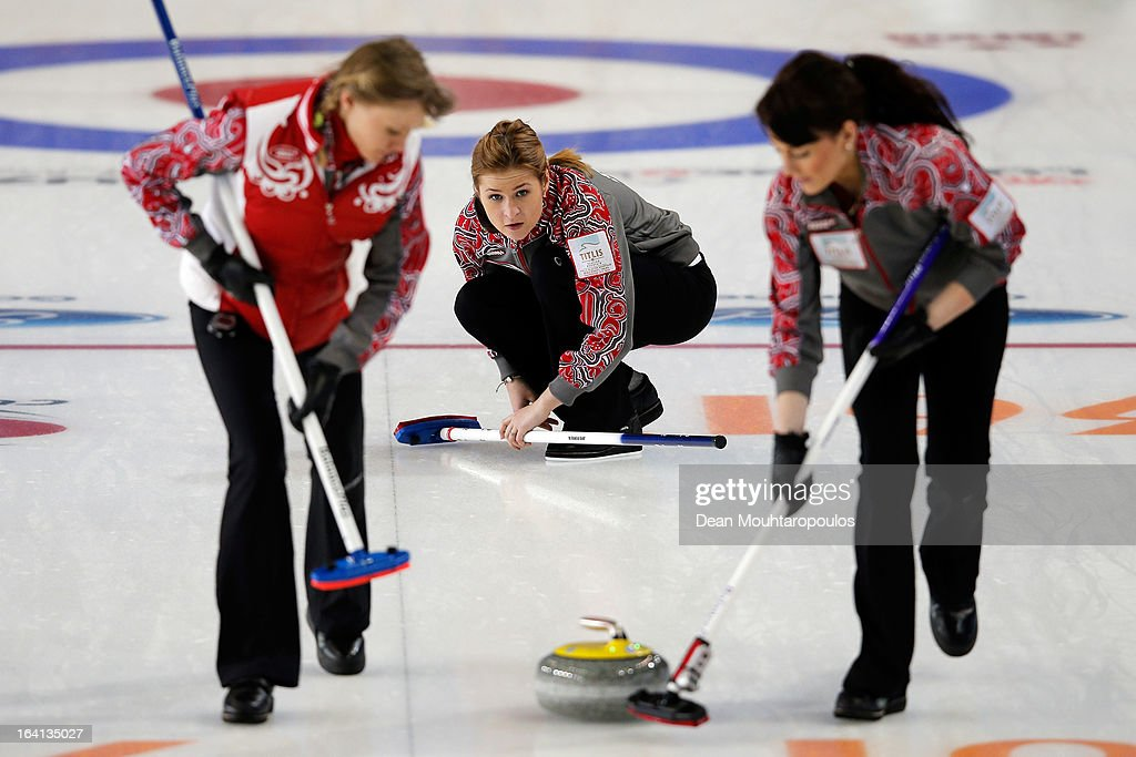 Margarita Fomina (C) of Russia throws the stone as Luidmila Privivkova (L) and Ekaterina Galkina (R) of Russia sweep in the match between Japan and Russia on Day 5 of the Titlis Glacier Mountain World Women's Curling Championship at the Volvo Sports Centre on March 20, 2013 in Riga, Latvia.