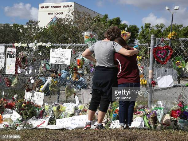Margarita Lasalle the budget keeper and Joellen Berman Guidance Data Specialist look on at the memorial in front of Marjory Stoneman Douglas High...