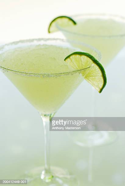 Margaritas with slices of lime on rim of glass