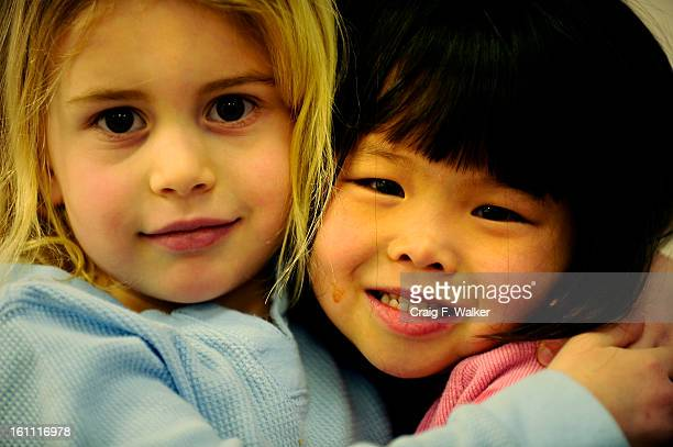 Margaux Harry left hugs her adopted sister Jade at the Chinese Children Adoption International campus in Centennial CO Saturday 22 2011 Lily Nie and...