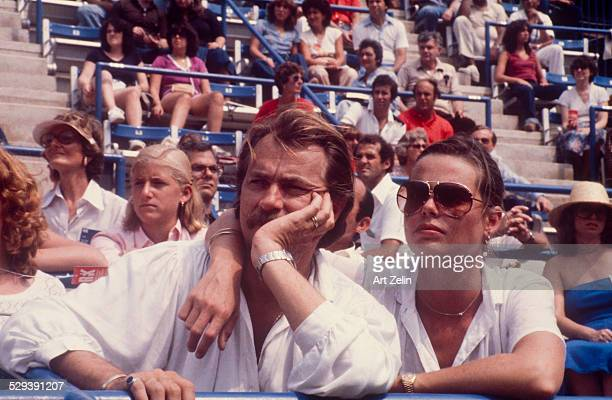 Margaux Hemingway in aviator sunglasses with a friend watching a tennis match; circa 1970; New York.
