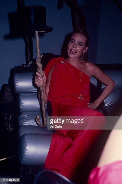Margaux Hemingway wearing a red dress holding a cane and top hat; circa 1970; New York.