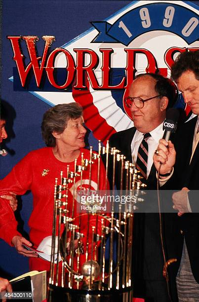 Marge Schott owner of the Cincinnati Reds and MLB Commissioner Fay Vincent are seen with the World Series trophy after World Series game four between...