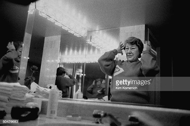 Marge Schott owner of the Cincinnati Reds baseball team primping in front of mirror in bathroom in her hotel room