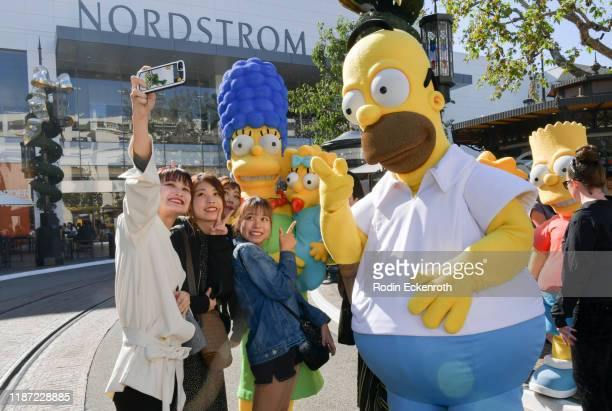 Marge Simpson Maggie Simpson and Homer Simpson take selfie with fans at the Disney Official US Launch Party at The Grove at The Grove on November 12...