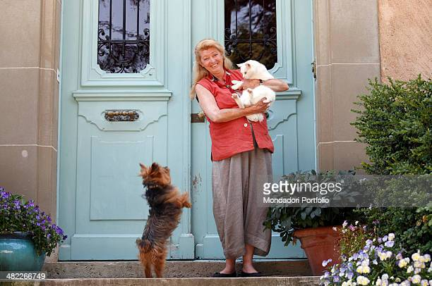 Margherita Agnelli de Pahlen posing on the threshold of her villa at Lake Geneva with a big white cat in her arms surrounded by vases of flowers and...