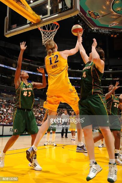 Margo Dydek of the Los Angeles Sparks goes up for a shot against Katie Gearlds and Ashley Robinson of the Seattle Storm on September 14, 2008 at...