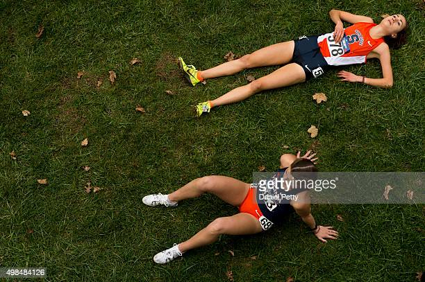 Margo Malone of Syracuse lies on the ground next to Sarah Astin of Virginia after finishing the women's 6K at the NCAA Cross Country Championships at...
