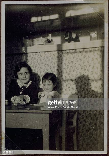 Margot and her sister Anne Frank sitting at a table The picture is from Margot's photo album