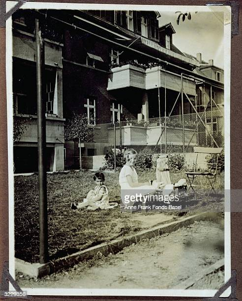 Margot Frank and her friend Butzy Konitzer sitting and playing with dolls in a yard Frankfurt am Main Germany From Margot Frank's photo album
