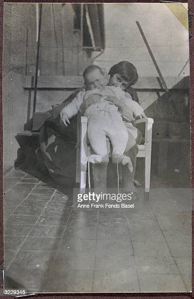 Margot Frank holding her sister Anne Frank on her lap while sitting in a chair on a balcony Frankfurt am Main Germany From Margot Frank's photo album