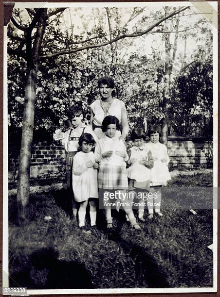 Margot Frank older sister of Anne Frank standing with a woman and children in front of tree blossoms in a garden From Margot Frank's photo album