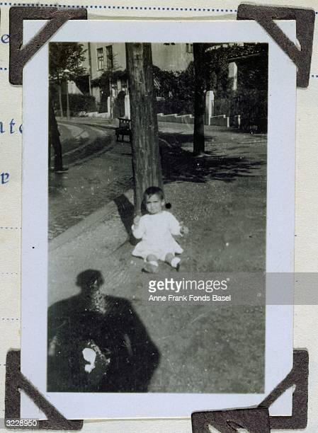 Margot Frank older sister to Anne Frank sitting against a pole with a person's shadow in the foreground taken from Margot's photo album
