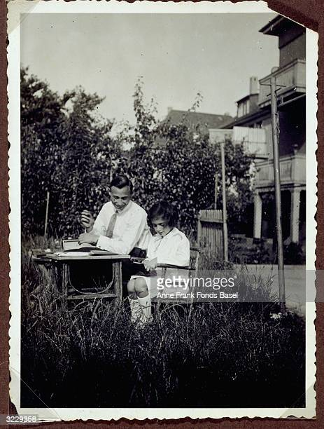 Margot Frank the older sister of Anne Frank and her uncle Siegfried Weihl sitting at a table in a garden Frank is opening a package as her uncle...