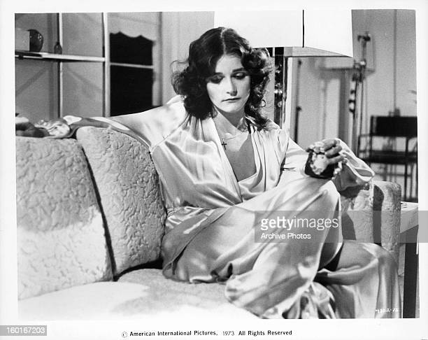 Margot Kidder relaxing on the couch in a scene from the film 'Sisters' 1973